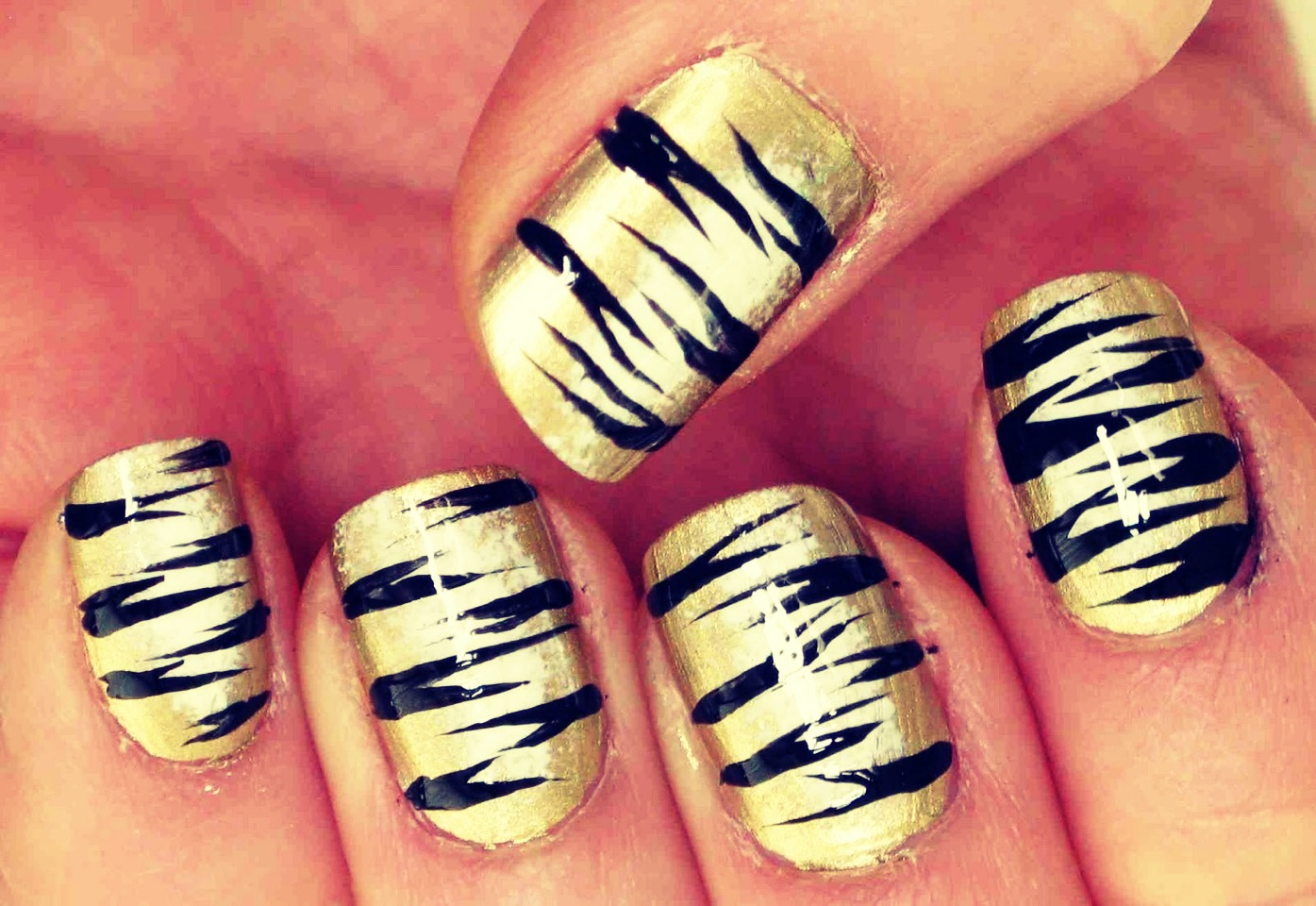 Use orange, gold, pink, yellow or light blue as your base. Take a black striper and starting from outer edges of your nail make a quick stripe in. After you have made stripes up the nail alternating sides. You can use black or a silver glitter striper to make second stripe under first stripes.