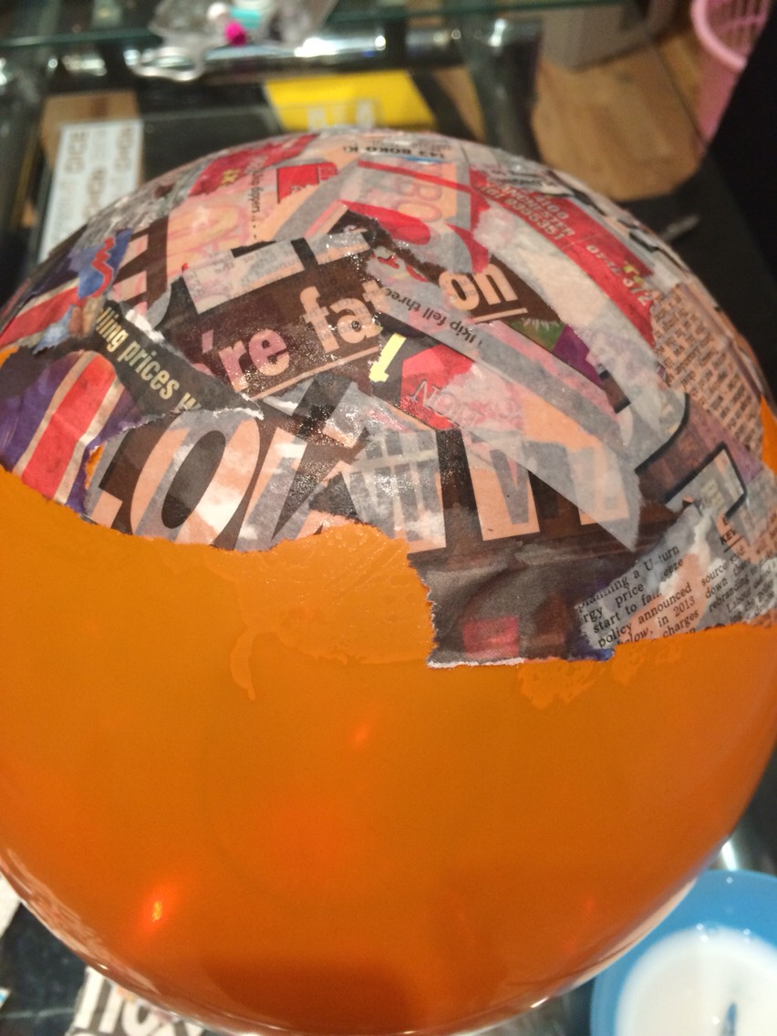 Start to add some of the thick liquid on your balloon and place newspaper on top all around the balloon