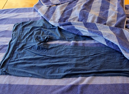 Then, get another dry towel and put the piece of clothing out on the dry towel.