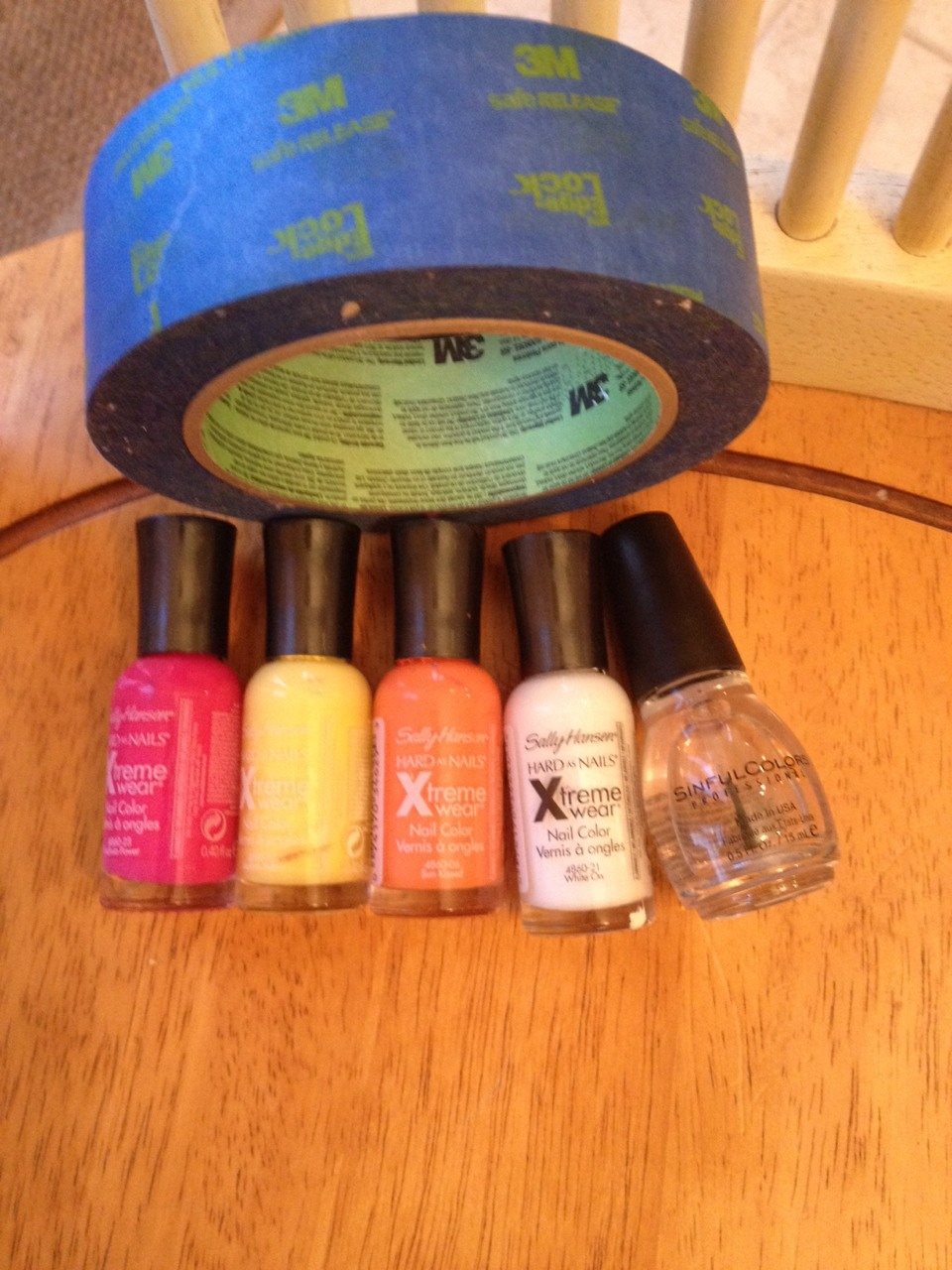 You will need some type of tape, a hot pink, yellow, orange, white, and a clear coat nail polish. I am using Sally Hansen Xtreme wear nail polish, and sinful colors clear coat, with edge lock tape.