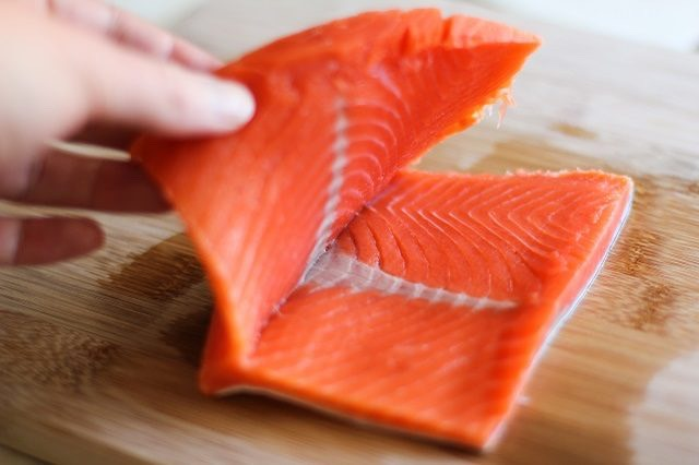 Tip  It's OK if you cut all the way through the salmon fillet. You can still stuff it by placing the slices one on top of the other.  Step 8. Stuff the Salmon  Use a large spoon to distribute the stuffing into the centers of each of the salmon fillets.