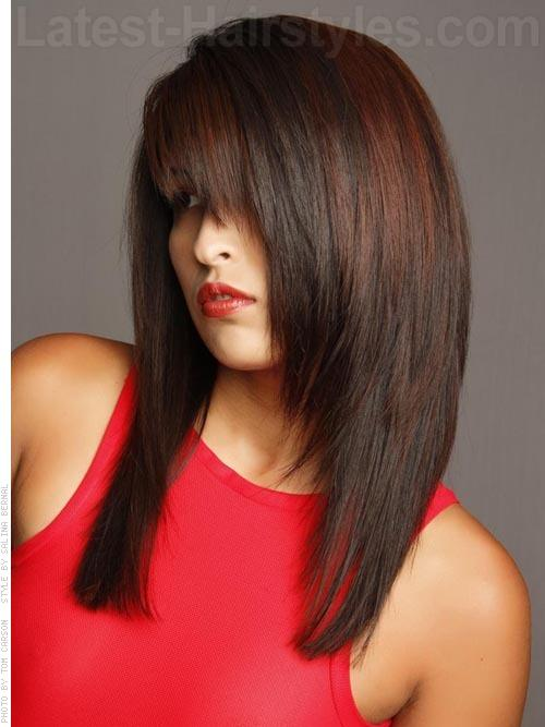 JAGGED LITTLE PILL These edgy face framing fringe and layers are complimented by ruby red accents that pop. The color also helps to show off the razored layers throughout the cut. The color and texture details are what really take this past the shoulder cut to the next level.