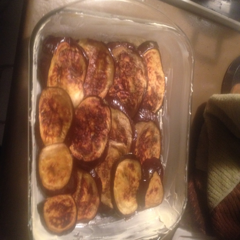 Baked eggplant with olive oil placed in a buttered pan