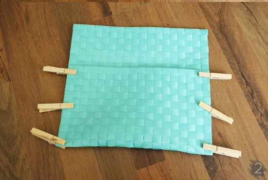 2. Fold the place mat while leaving about 4 inch on top to fold over the opening of your clutch. Glue the sides and use clothespins to keep material in place while it's drying. Remove the clothespins when the glue is dry.