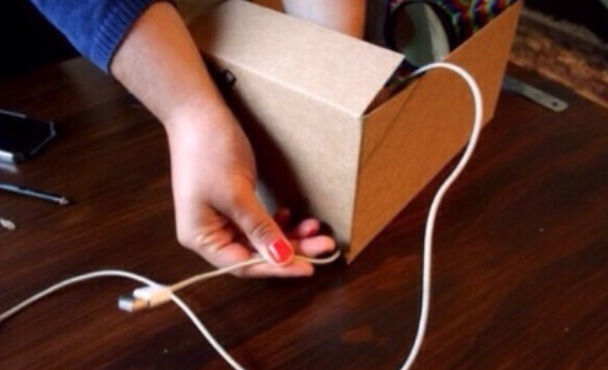 Poke a hole in the back of the box and slip your charger through.