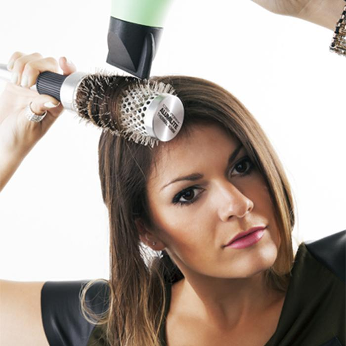 Using the dryer and a medium-sized round brush, blow dry the first section of your hair. Hover the dryer as close as possible to the brush, and keep them in line as you work slowly from root to tip. Once you've reached the tip, cur e brush under to add dimension to your locks. Repeat until dry.