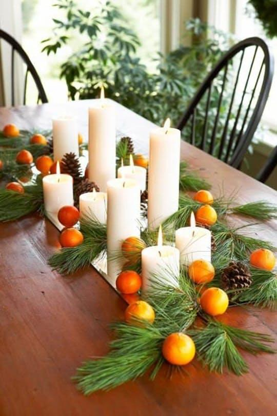 A few holiday clementines, greens and pinecones you can collect in your own backyard, and simple pillar candles make for a lovely display, like this one fromMidwestLiving.