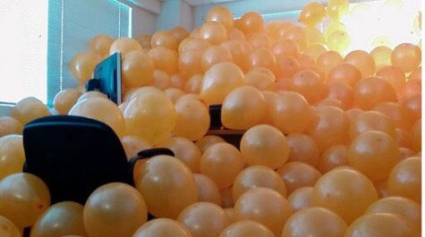 Fill the room up to the top with balloons, hide in the balloons and when they walk and jump up and scare them.