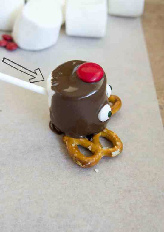 The stick goes in first, then dip it in the melted chocolate. Put an M&M on for the nose, then the eyeballs on. Lay it on top of two twisty pretzels and let it dry laying down on a sheet of wax paper.  DONE!