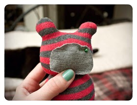 7. Cut out a piece from the other sock to create his little muzzle. Cut out an oval shape – I'd say close to the size of his face and then pin it in place.