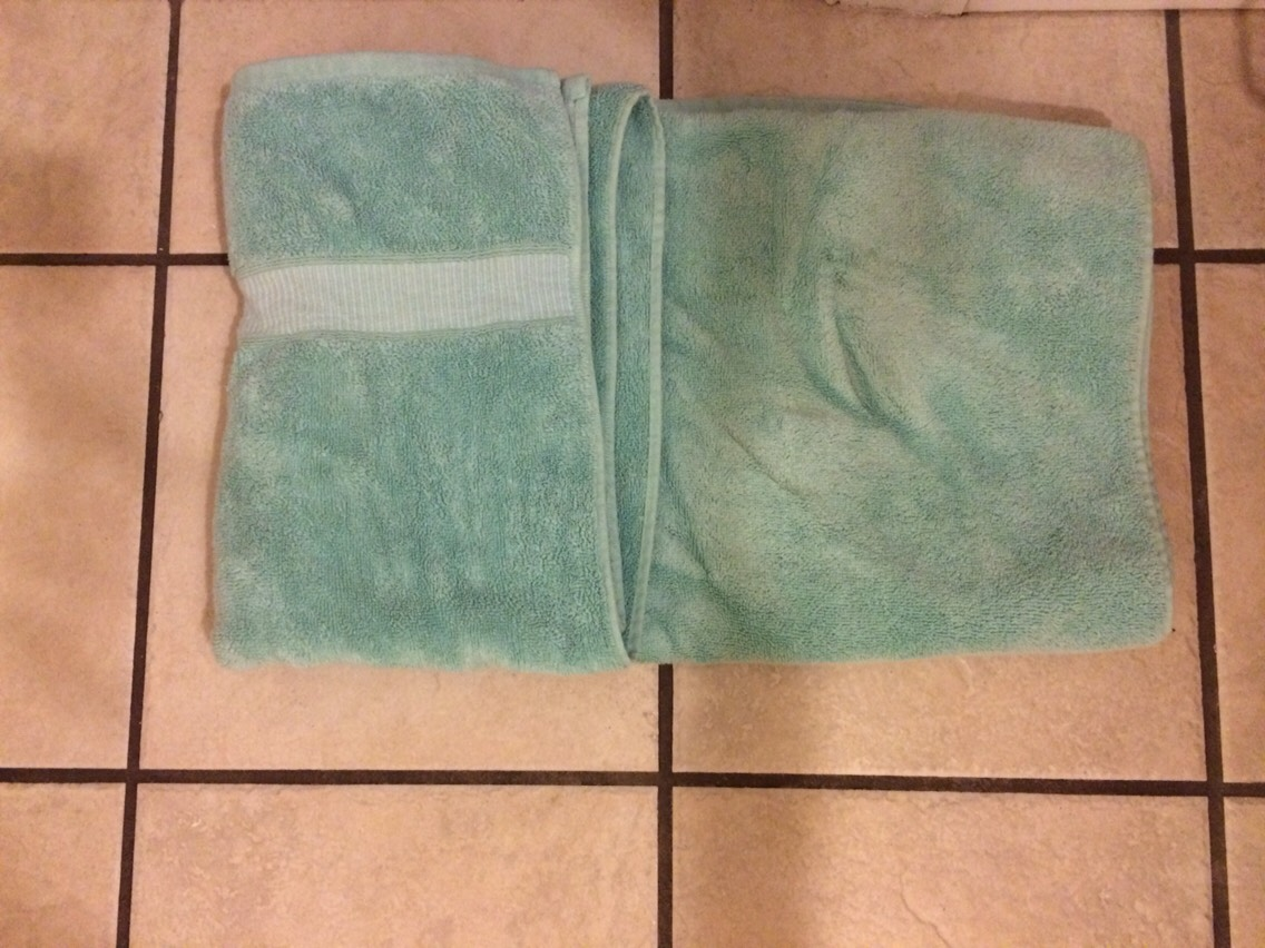 4. Take one side of the towel and fold it over about 1/3 of the way, maybe a little bit less
