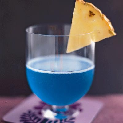 Blue Hawaiian  1½ oz coconut rum 2½ oz pineapple juice 1 oz blue curacao pineapple wedge, for garnish Combine coconut rum, pineapple juice, and blue curacao in a cocktail shaker filled with ice and shake vigorously. Strain into a chilled martini glass. Garnish with a pineapple wedge