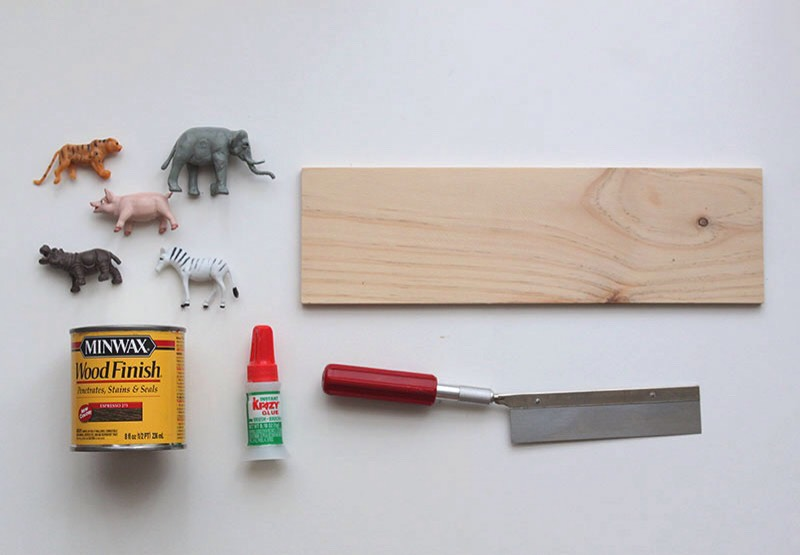 Materials:  – Plastic Animals (I bought these at Michaels) – Piece of wood (Mine was 12″ x 3.5″) – Mini Saw – Super Glue – Drill – Wood Stain (Optional)