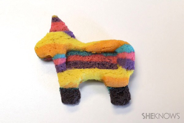 """and one burro piñata cookie in the opposite direction. (Just flip your cookie cutter over.) That way, when you go to assemble them, the finished cookie will look """"pretty"""" on both sides -- because the baked, bottom sides will be hidden. For the middle cookies in each set, cut off the ears and legs"""