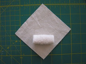 "4. Place the folded batting onto the 4""x 4"" fabric diagnally, than stard wrapping it like making a spring roll. Use pictures as a guide."