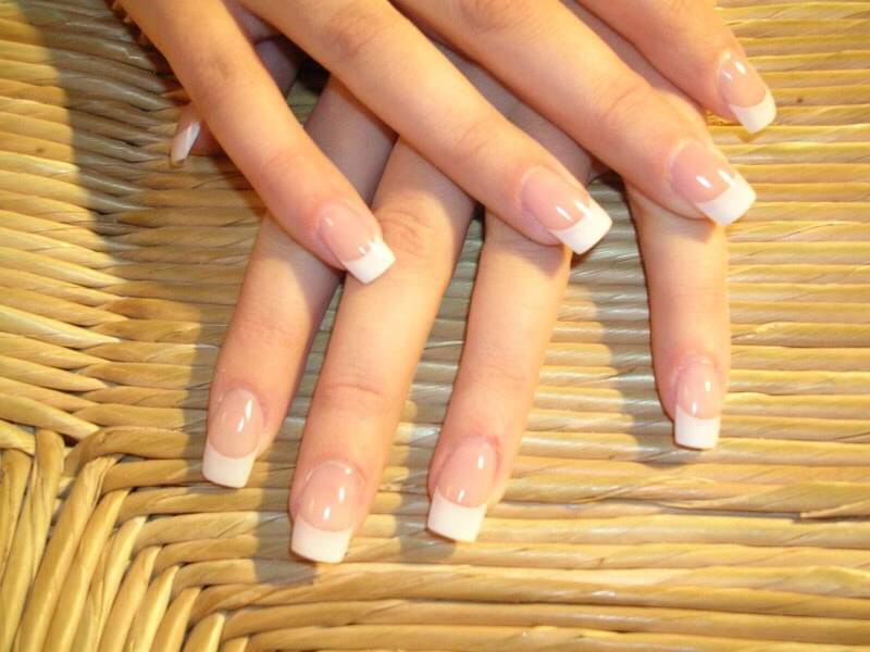 Rubbing alcohol won't damage your nails very much. So, soak a cotton ball in rubbing alcohol and leave on your nails for about 10 minutes. Then, you can either lift the acrylic nail off or take a piece of dental floss and work it under the nail.