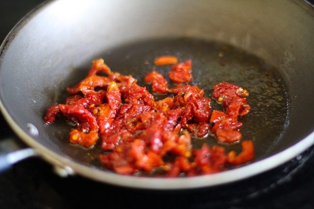 Step 3. Add the oil and chopped sun-dried tomatoes to a skillet over medium heat. Cook for 1 minute, stirring occasionally or until fragrant.