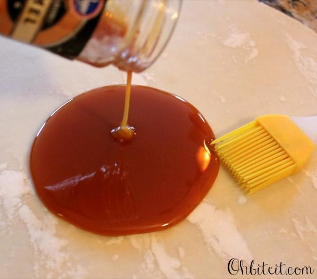 Pour some of the Caramel Sauce (Just enough to coat the crust) onto the crust and evenly spread it around, creating a thin layer of caramel