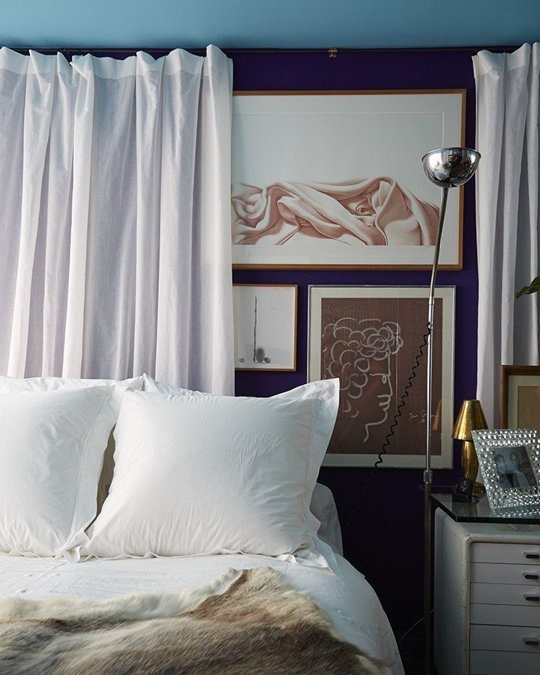 A curtain hung behind the bed is another greay way to dress up your sleeping space, with or without a gallery wall concealed behind. Image fromLonny.