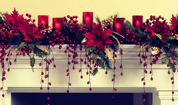 Real pretty way to light up your fire place with some of these red flowers and candles