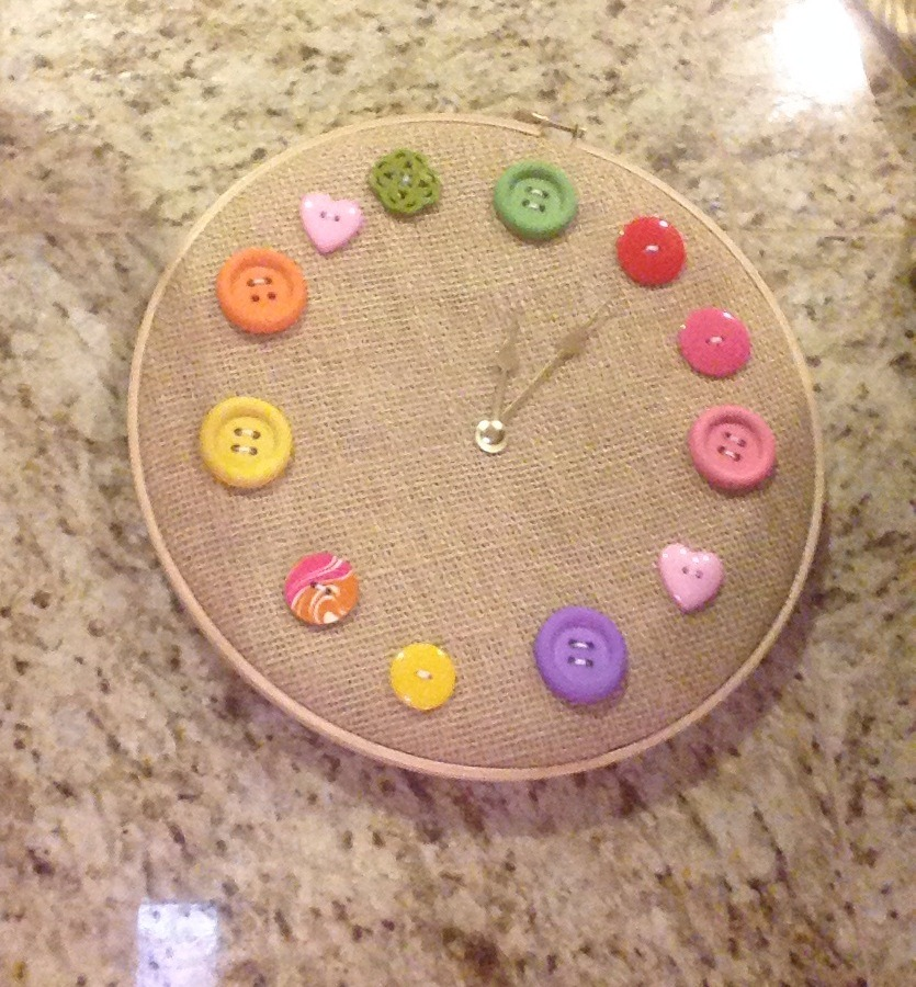 Hoop, $3 craft store Colorful buttons Doubled up burlap and needle and thread! I just used the wall clock hands and inserted a thumb tac to keep it inexpensive. Also it won't be as heavy. I just wanted it as a decoration