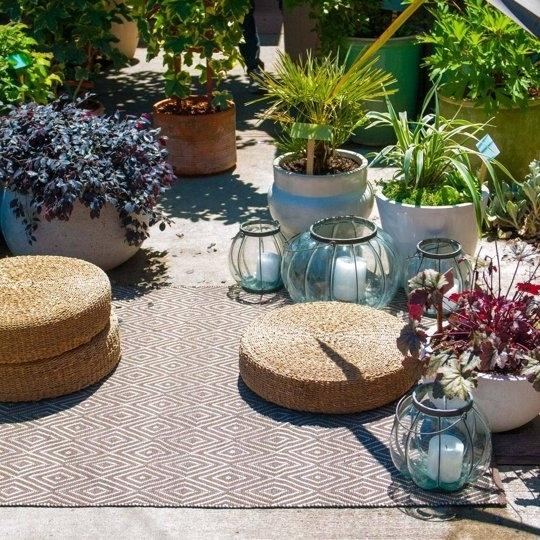 Create a backyard hangout spot with pillows, a rug, lights, and plants.