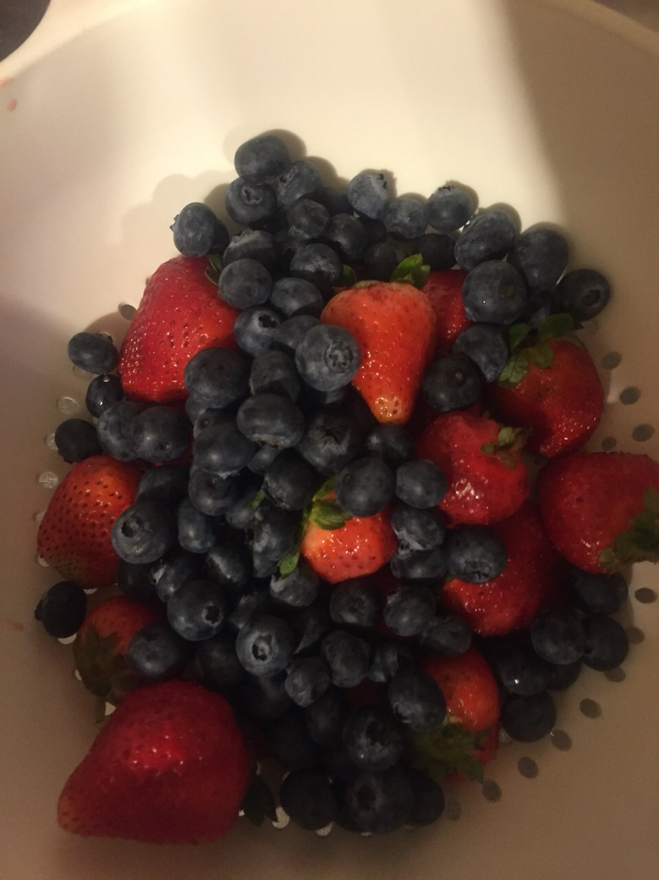 Put all your strawberries and blueberries inside a strainer.