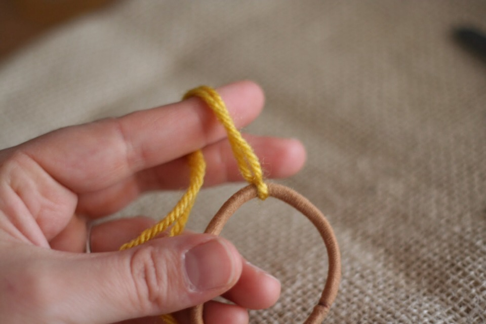 Tie the string to a hair tie and start braiding down and then tie the other end to the hair tie.