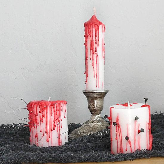 To create Halloween taper candles, squish a small length of tinfoil and wrap around the base to help the candle stand on its own. Now drip the red wax at the top of the candle until it runs the length of the candle.