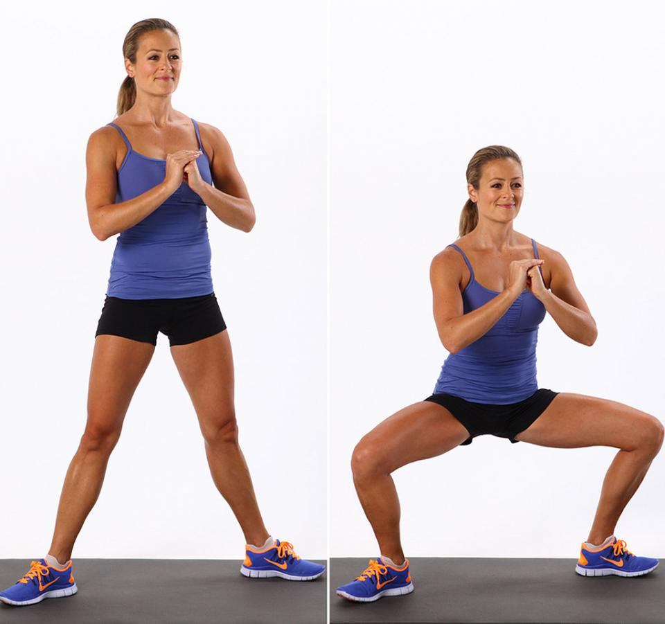 Wide Squat Hold a pair of dumbbells in your hands with your arms straight and your palms facing away from you. If you don't have dumbbells, keep your hands clasped in front of your chest as shown. Step your feet apart so there's about 20 inches between your heels. Point your toes out slightly.