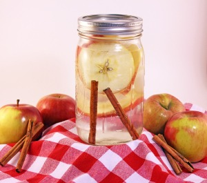 Cut apples into slices and put them into the bottom of a mason jar. Cover the apples with water and place two cinnamon sticks inside.