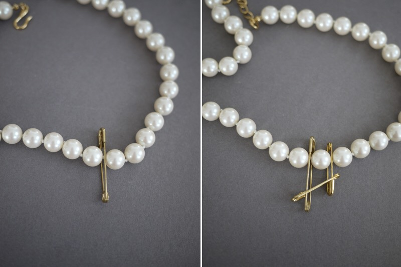 Start in the center of the necklace and attach 1-2 safety pins between each pearl, working outwards. Connect the vertical safety pins with a horizontal one.
