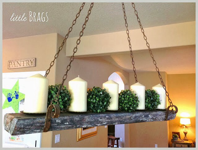 A reclaimed wood candle chandelier can be as easy as a plank of wood, some rusty brackets, chain, and candles... or lights! What a cool look!