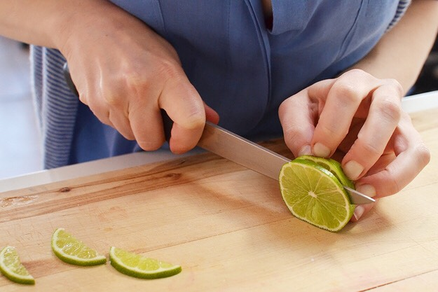 Slice lime (you can use the same one if you don't care about the aesthetics, or a new one if you do) into thin rounds, then cut into small wedges. You may also want to cut a small chunk through the center of each wedge's flesh so they can balance on the tip of the strawberry.