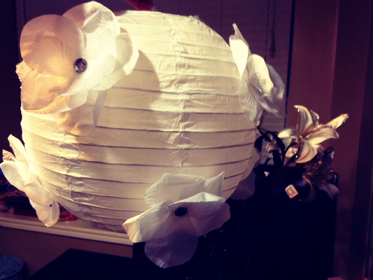 Dress up a paper lantern; great for wedding decorations!   All you need is:  Paper Lantern Silk Flowers Gem stones Hot glue gun  Take the petals off of the silk flowers and arrange them accordingly, then glue a gemstone in the middle. Glue each arrangement onto the paper lantern and you're done!