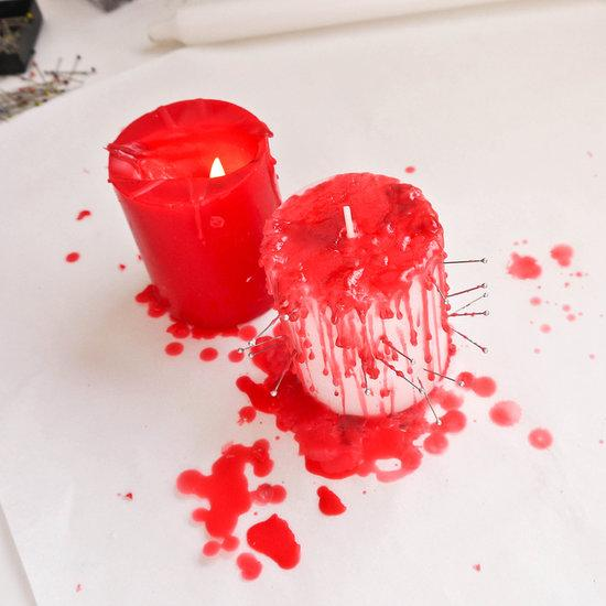 Now light the red pillar candle and get ready to drip some goulish wax blood. Start pressing cut tacks into a white pillar candle and dripping wax over the top, making it look like the pierced candle is gushing blood. You can find cut tacks at your local hardware store for around $2. Remember to