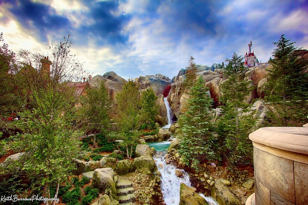 Walt designed the parks so when you pass from land to land, you don't see the others.  If you were in Liberty Square, you can't see Fantasyland because of the trees, buildings and other distractions. The parent colours are also different in each land to match the mood.