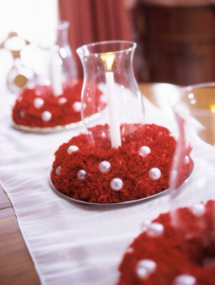 """Carnation candle holders  Encircle glass hurricanes with carnation """"wreaths"""" for a pretty Christmas tabletop. Create the wreaths with florist foam wreath bases, scarlet carnations and small ball ornaments."""