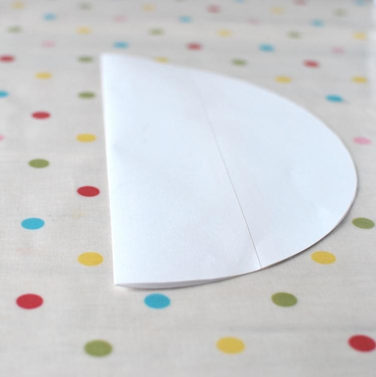 Take the paper circle and fold it in half.