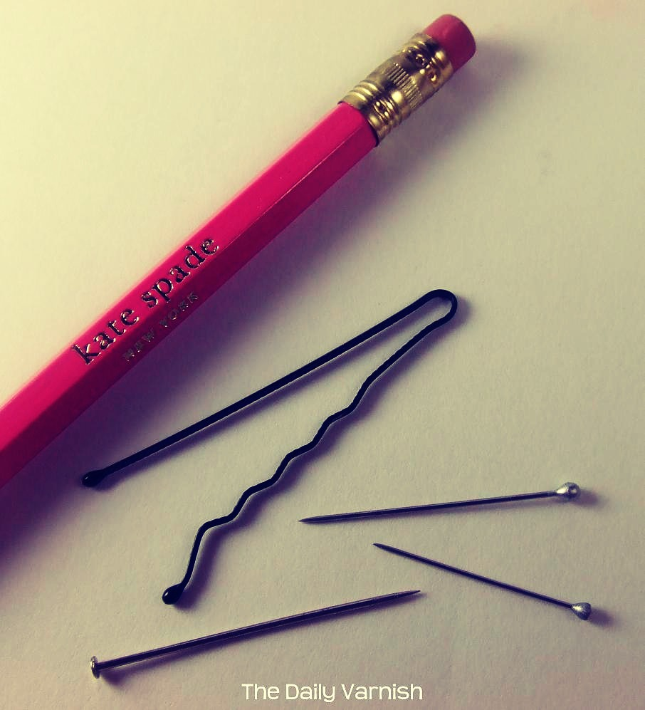 1. Use a bobby pin 2.use a tooth pick 3. Uses ball point pen 3 use a straight pin from your sewing kit--join pin to a pencil w/ an eraser end to provide better leverage and balance 4. Use a paintbrush--- just flip the brush over and use the end