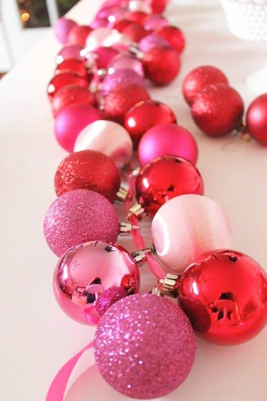 String together some ornaments using ribbon and run them down the middle of the table like in this tutorial byediTORIal.