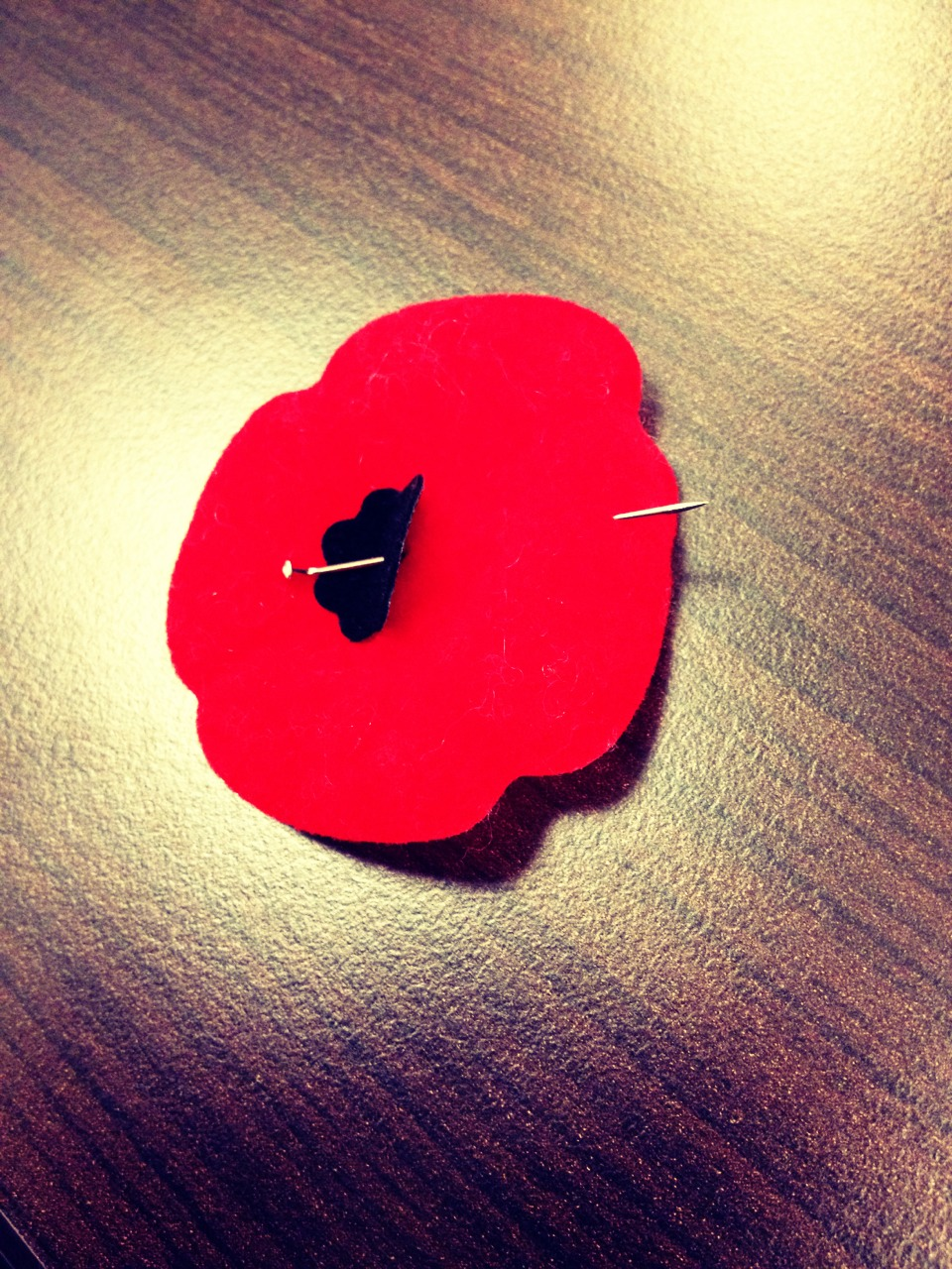 Slide pin through the poppy twice, stick close to the outer most edge of the poppy so it will keep a pretty shape.
