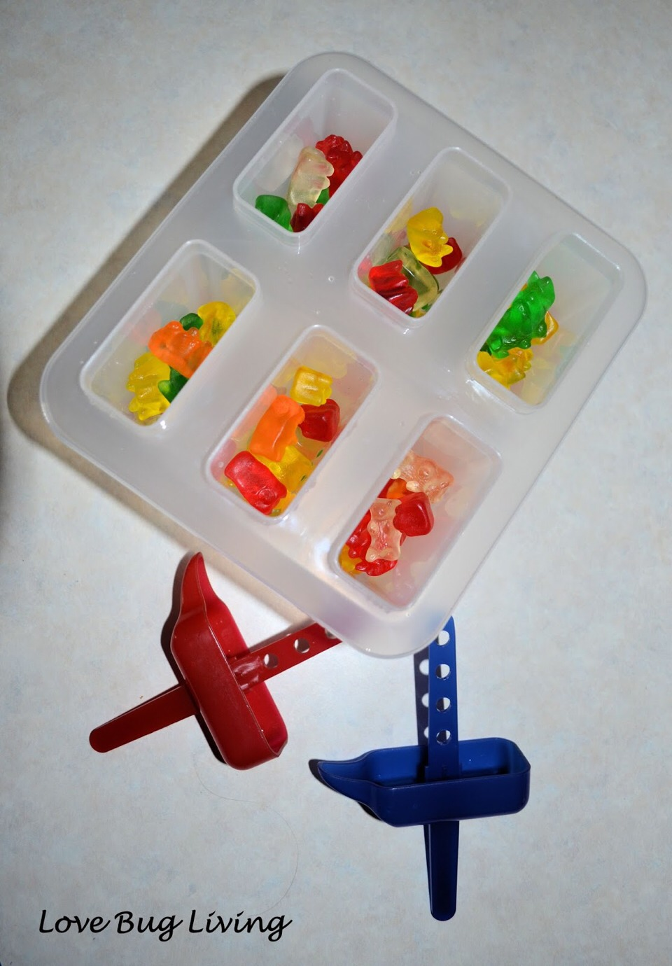 Next put the gummy bears and sprite in the popcicle thing