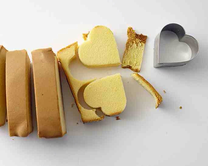 """INSTRUCTIONS   STEP 1) CUT OUT CAKE HEARTS   Slice the pound cake into 1"""" slices. Lay slices flat and use the 1 7/8"""" heart cutter to cut two hearts from each slice. (Save scraps for cake pops!) Place the cake hearts on a sheet tray fitted with a cooling rack."""