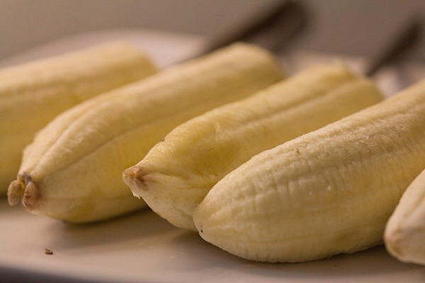 Get your bananas (as ripe as you like) and place on a tray which will fit in the freezer. put a lolly stick or BBQ skewer through and then place in the fridge for 15 or so minutes To chill, in order to harden them slightly so they're easier to coat....