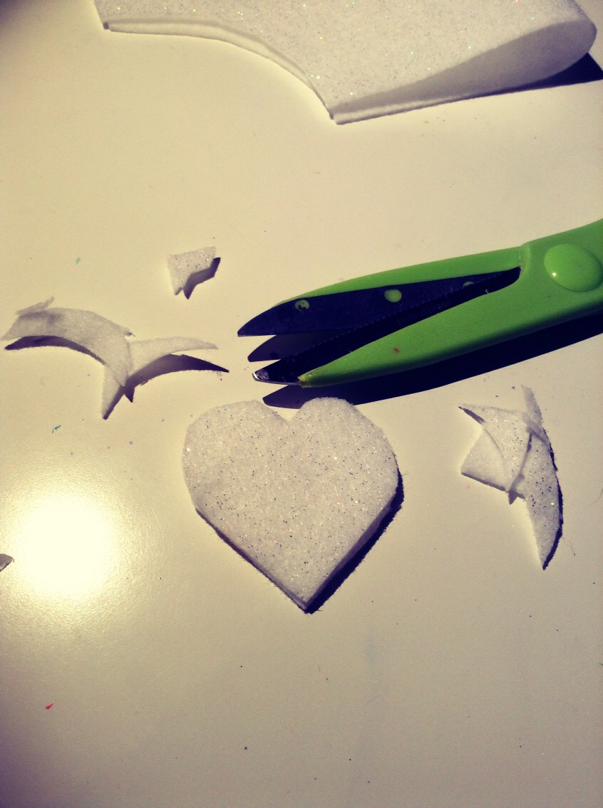 Using your scissors cut the corner into a heart. Keep 2 hearts together.