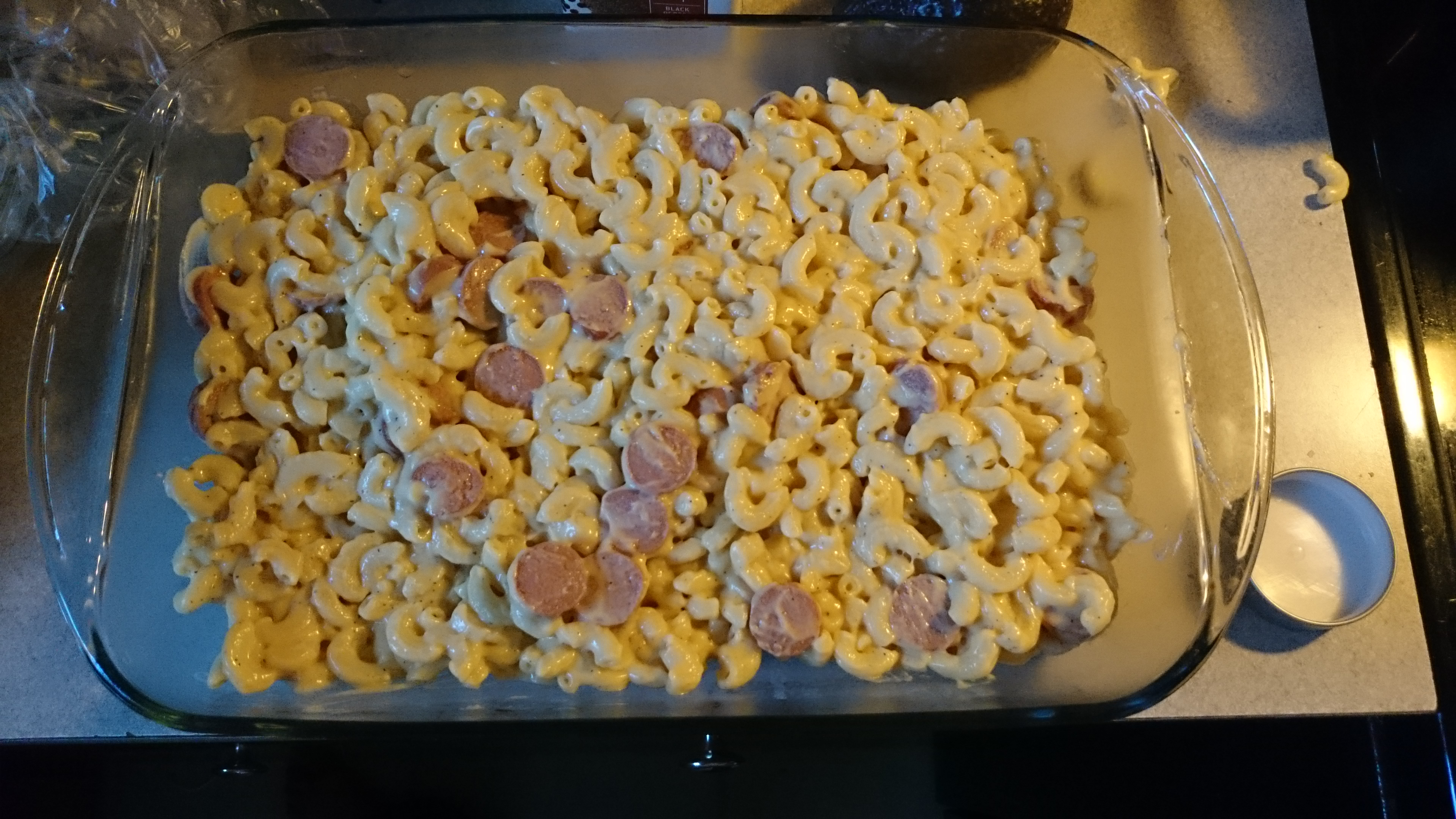 Pour the Mac 'n' cheese with sauce into a separate pan and then sprinkle some cheese on top.