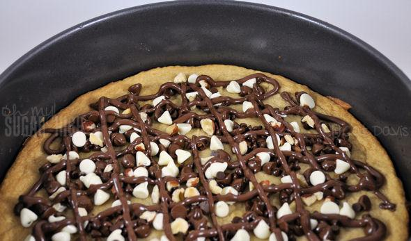 4. Sprinkle the baking chips evenly over the cookie, leaving the edges free so you'll have a non chocolate surface to hold your pizza slice.  5. Using a piping bag (or use the corner of a plastic sandwich bag) spread the Nutella over the baking chips in any design you like.