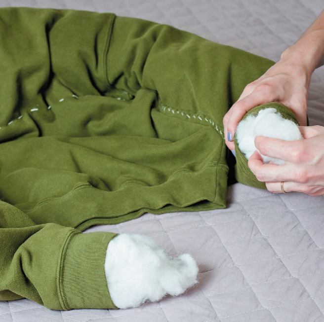 Insert acrylic blanket, foam or even chopped leftover fabrics through the cuffs to form the edges of the bed.