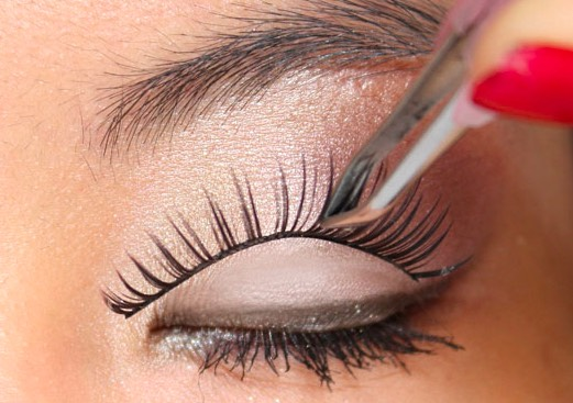 The best way to apply eyelashes is to use a tweezers.  Start by holding the middle and putting that in place waiting 4-5 seconds then sticking down either side.  Use a closed tweezers to pat down along the lash line to make sure it's securely in place.